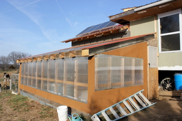 A south facing sun room/greenhouse provides growing space and warmth.  In the winter, the residents open the door to their house, and let the warm air from the sun room enter.  In the summertime, they shade/screen the sun room.